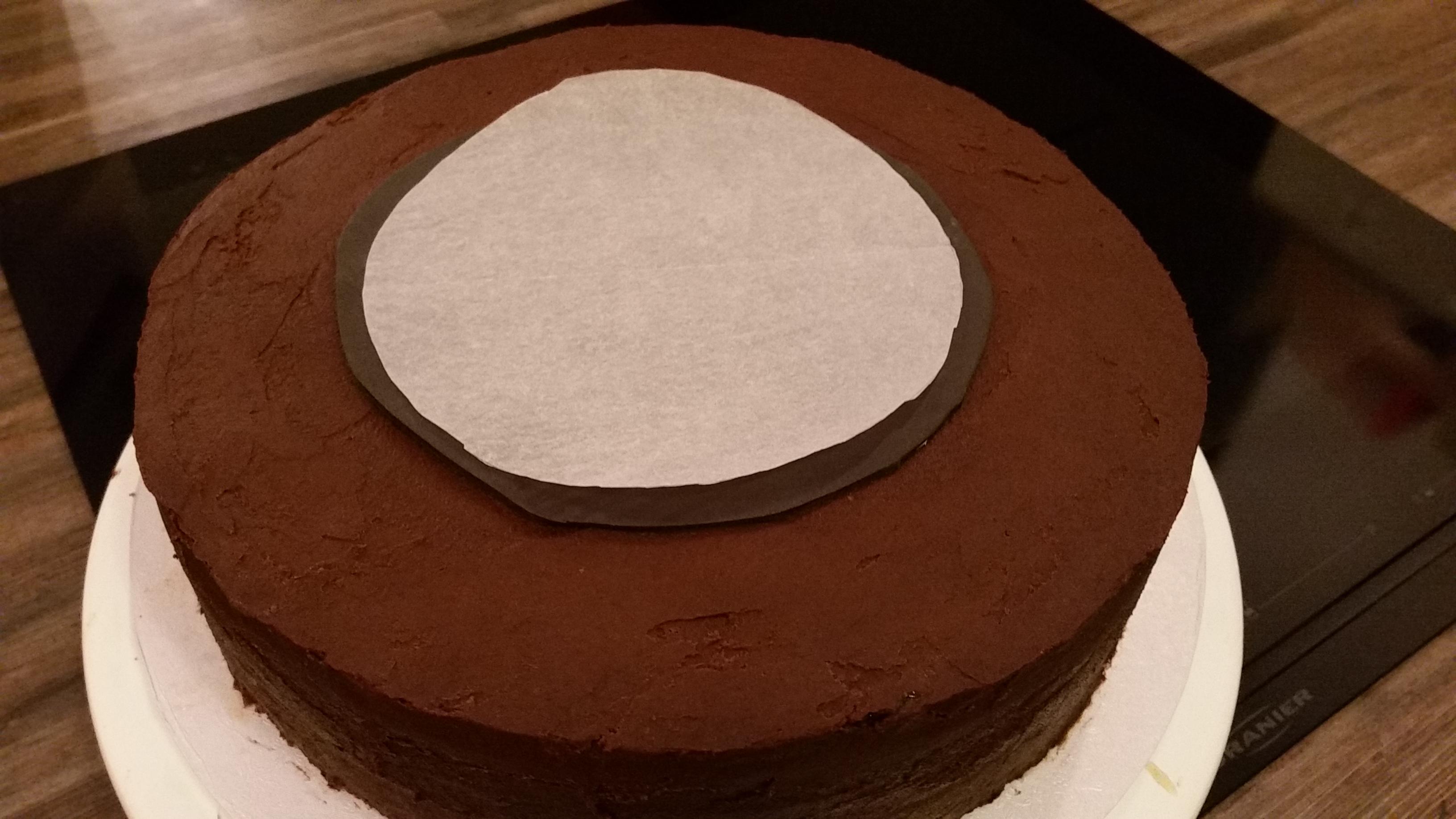 Danach 2x ein Backpapier rund ausschneiden, in etwa der Form des Kreises, gerne etwas kleiner. Eines davon, direkt auf den schwarzen Fondantkreis legen.
