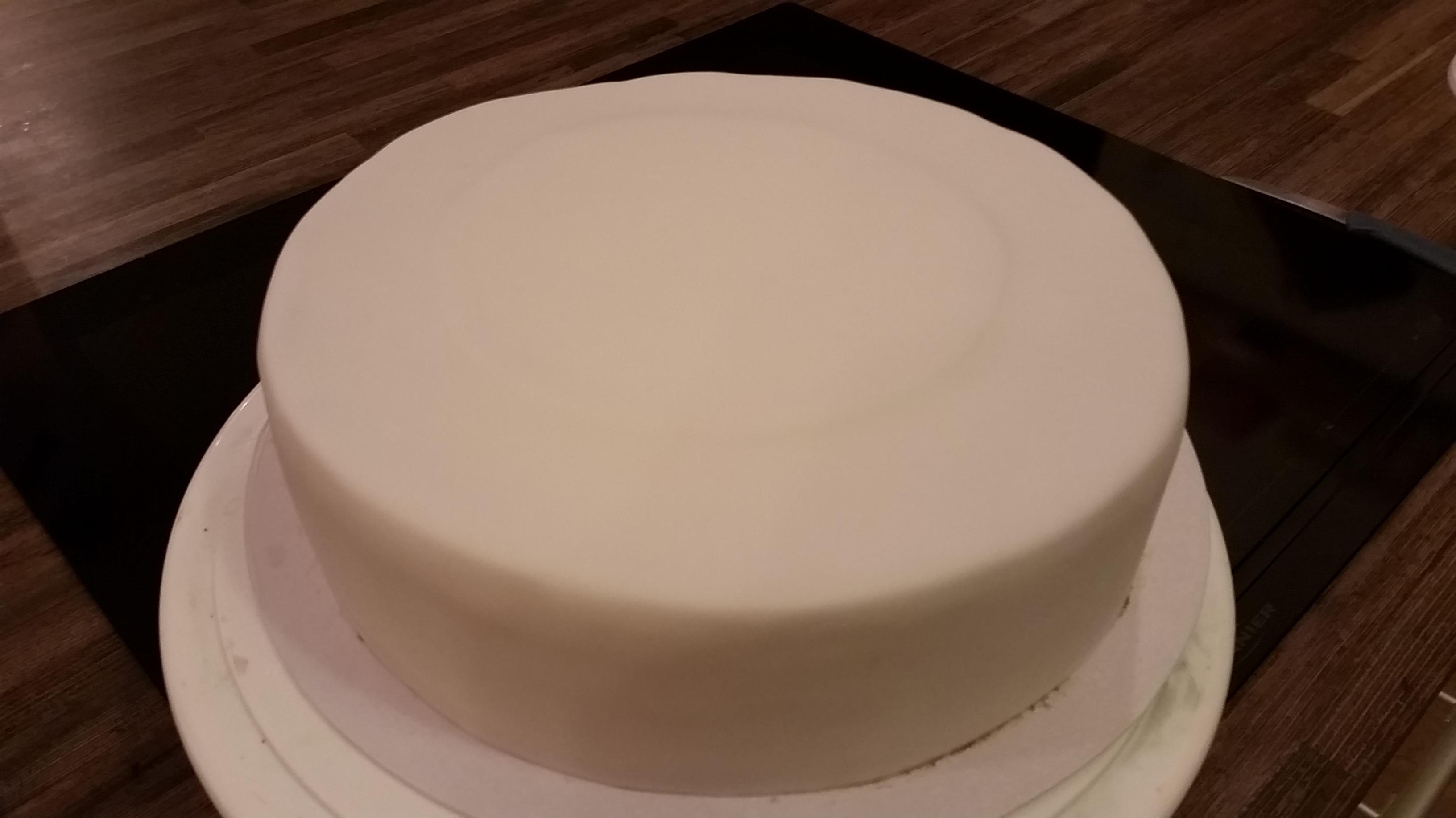 Die Torte normal mit weißen Fondant überziehen.